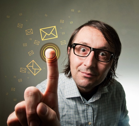 Nerd looking male using a touch screen to check his e-mail inbox, pressing an envelope representing an incoming e-mail message. Futuristic technology concept. Stock Photo - 12064355