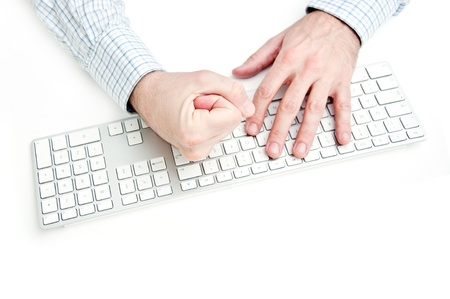 Angry businessman hits the computer keyboard on a white desk top. photo