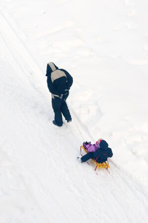 FAther pulling sledges in snow with his children. photo
