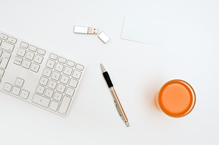 Office desktop, a keyboard, pen and a usb flash drive. Stock Photo - 12329636