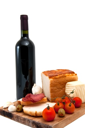 cheese plate: Gluten free bread with olive, red cherry tomato, garlic, cheese, sliced red smoked meat and a bootle of red wine. Stock Photo
