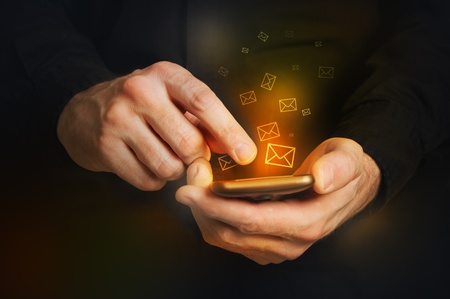 e work: Man in black shirt is typing a text message on his smartphone, close up image, focus on hands and the phone device  Stock Photo