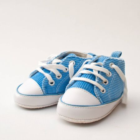 pie bebe: par de zapatillas para beb�s azules y blancas sobre un fondo gris claro Foto de archivo