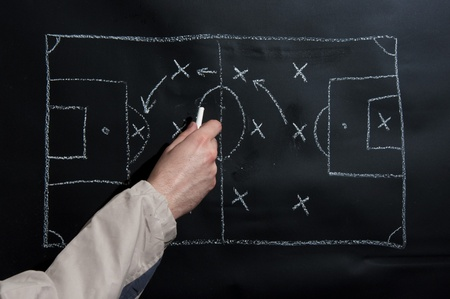 Man drawing a soccer game tactics and strategy with white chalk on a blackboard
