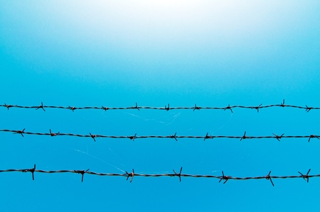 barb wire: Barbed wire fence against the blue sky Stock Photo