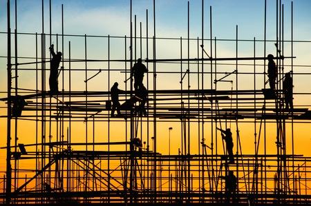 Obra de construcción, las siluetas de los trabajadores en contra de la luz /
