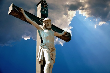 grunge cross: A statue of Jesus Christ crucified against dramatic sky Stock Photo