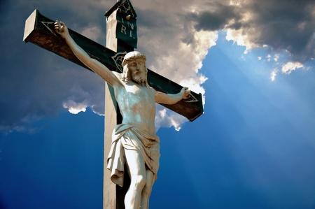crucified: Una estatua de Jesucristo crucificado contra el cielo dram�tico Foto de archivo