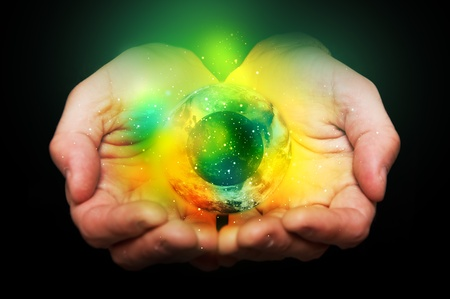 hand holding globe: Hands holding a glowing yellow and green sphere in hands
