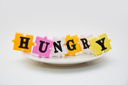 "ni�os pobres: Colorido palabra ortograf�a rompecabezas de la palabra ""hambre"" en un plato vac�o."