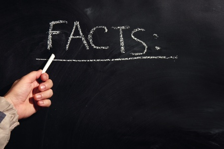 Male hand is writing FACTS with the chalk on the black board Stock Photo