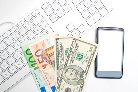Office desktop, a computer keyboard, smart phone communicator and couple of dollar and euro bills. Stock Photo - 13020674