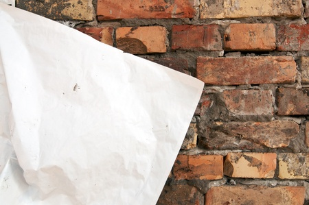 Blank torn paper poster on an old brick wall photo