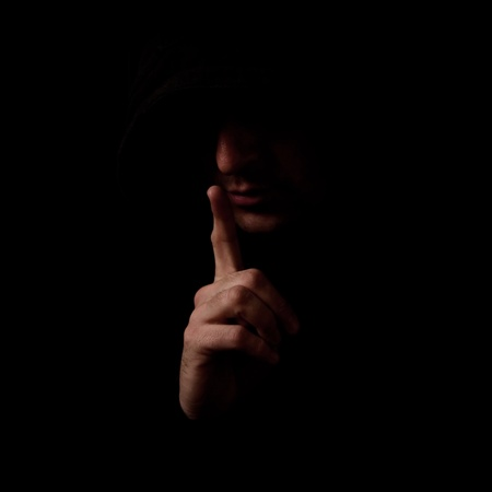 low light: Man in the low light interior holding index finger over his mouth, making a Shh gesture