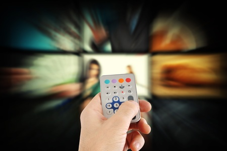 Man using a remote control and changing TV channels  Stock Photo