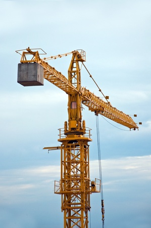 cranes: Yellow construction crane on a cold, cloudy day. Stock Photo