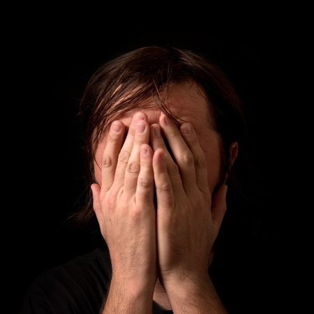 Crying man with hands covering his face in low light interior  Stock Photo - 13268909