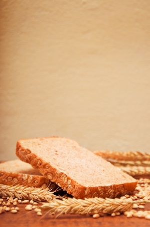 Wheat bread and grains and wheat ears on a wooden table Stock Photo - 13324023