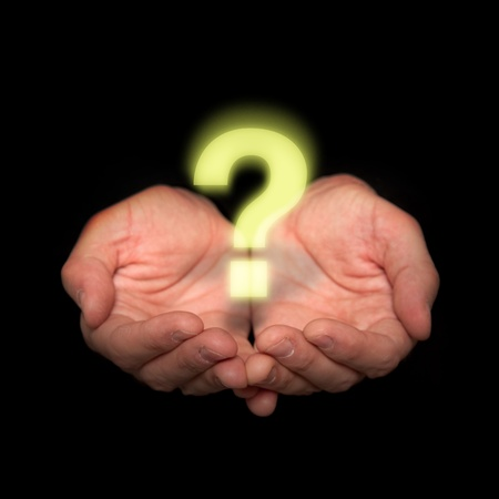 Male hands on a dark background holding a bright question mark photo