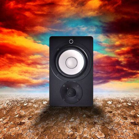 Speaker on a dry desert land against a blue sky with clouds photo