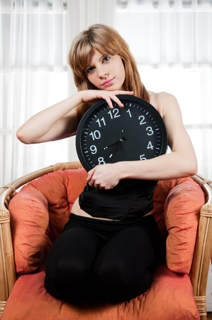 Portrait of a young woman with a clock photo