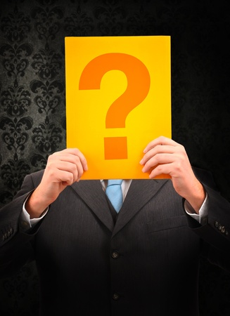 bad leadership: Businessman holding question mark in front of his head on vintage background Stock Photo