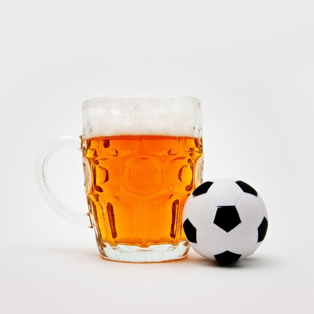 Glass of cold beer and a small soccer ball photo