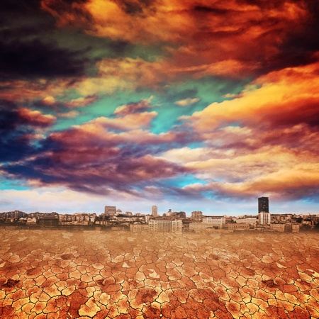 Dry desert land against a blue sky with heavy clouds, city in the background. Global warming concept. photo