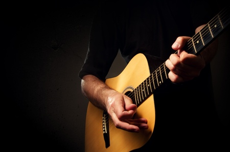 stage performer: MAn is playing an acoustic guitar in low light environment