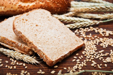 Wheat bread and grains and wheat ears on a wooden table photo