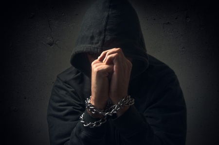 prisoner man: Male hands with chain wrapped around them, prisoner concept Stock Photo