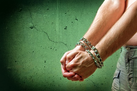 restraining: Male hands with chain wrapped around them, prisoner concept Stock Photo