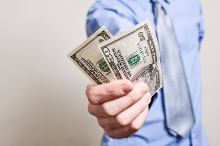 bribe: Businessman is paying in dollar bills, corruption and bribe concept.