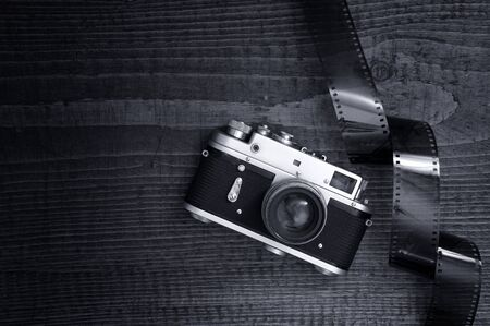 Retro style camera on a wooden table plate with some 35 overexposed film strip photo
