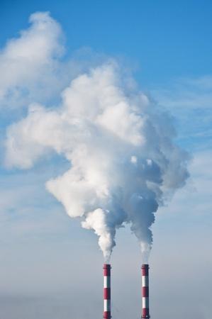 desechos toxicos: Calefacción chimeneas de las plantas contra el cielo