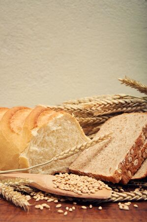 Various sorts of bread with wheat grain and ears on an old wooden kitchen table  photo