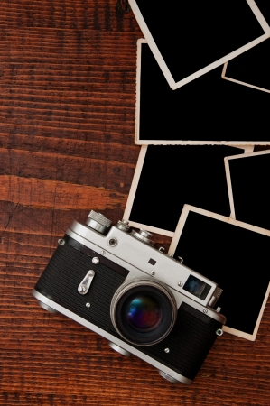 Retro style camera on a wooden table plate with some blank photo frames photo