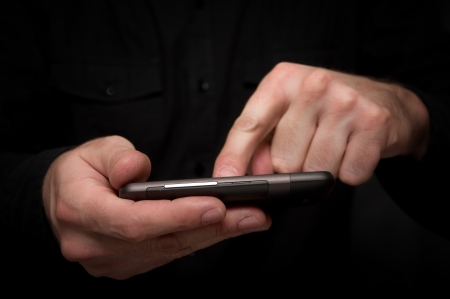 Man in black shirt is typing a text message on his smartphone, close up image, focus on hands and the phone device. photo