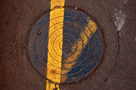 utilities: Background or texture  Cast iron sewer manhole lid flush with sidewalk Stock Photo