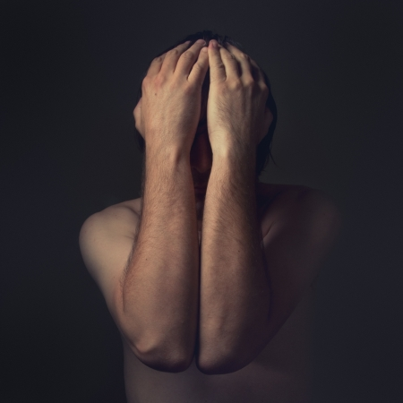 Sad man is covering his face with hands and crying in despair  Stock Photo - 13781880