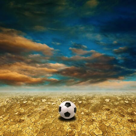Soccer ball on a dry desert land against a blue sky with clouds photo