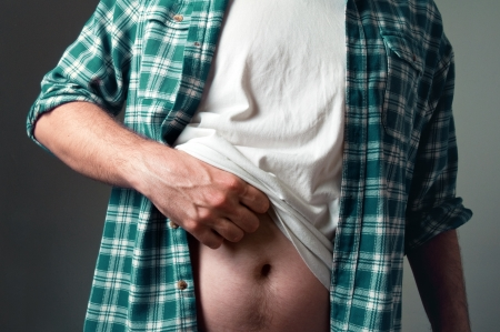 Casually dressed man is scratching his belly photo