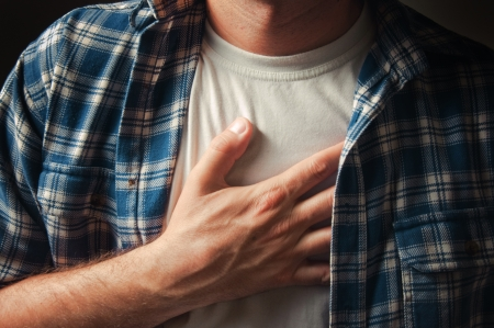 Young adult man suffering from severe chest pain.