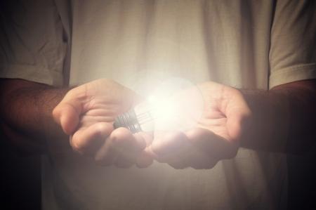manos abiertas: Las manos abiertas de un hombre con una bombilla de luz Foto de archivo