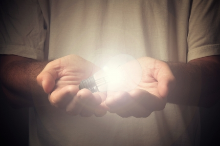 hope symbol of light: Open hands of a man holding a light bulb