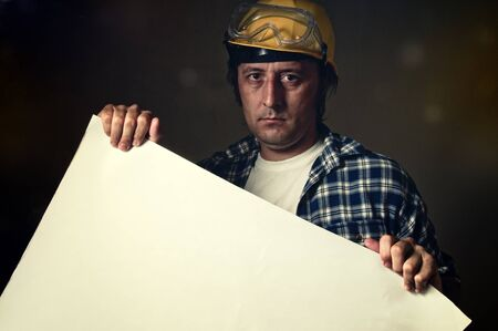 Construction worker with yellow hard hat and protective goggles in dark environment holding a piece of blank white paper. Workers strike concept. photo