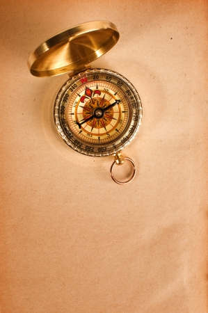 Vintage compass top shot over a grungy yellow paper photo