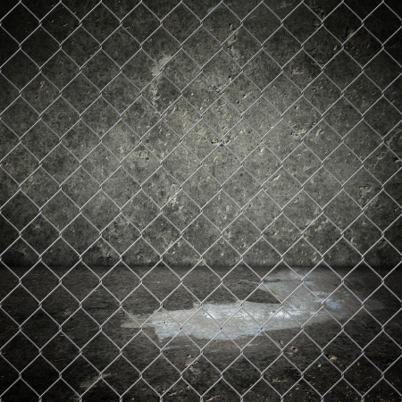 Obsolete gray grunge concrete room closed with chain link fence  photo