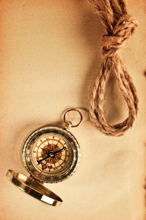 orienteering: Vintage compass top shot overa grungy yellow paper Stock Photo