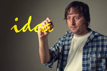 imaginative: Young adult casual designer writing the word  Idea  with yellow pen marker in the air  Stock Photo